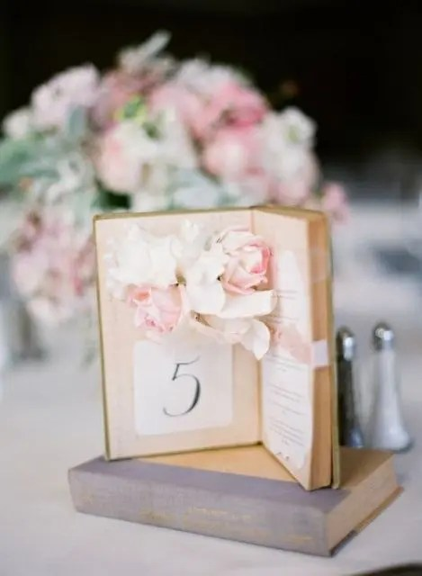 a book plus an open book with a table number and some fresh blooms attached inside for a romantic touch
