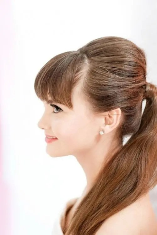 a ponytail with a bump and bangs is a cool idea for cuasl brides who don't want much fuss with their hair
