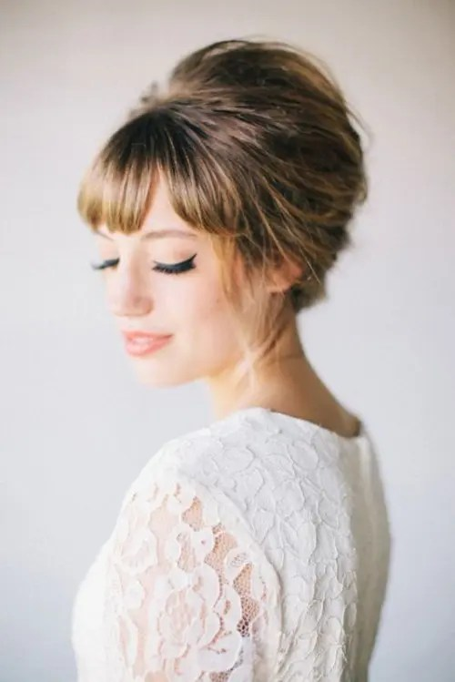 a full fringe bang with a retro-inspired updo and matching makeup for a retro-inspired wedding