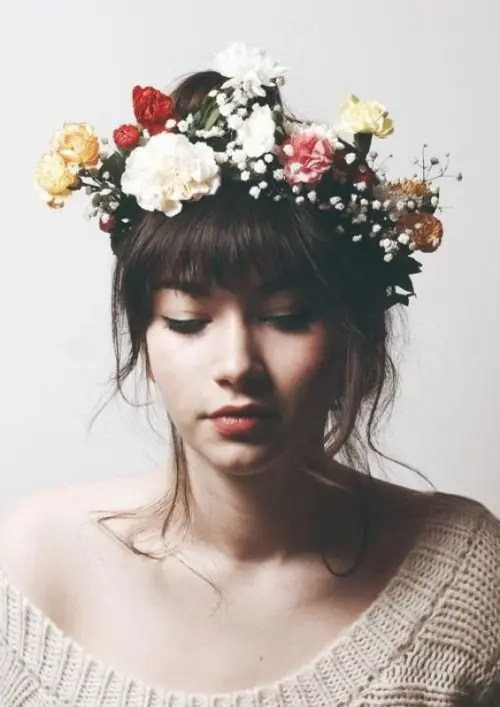 a wavy updo with long wavy bangs and a colorful floral crown with baby's breath