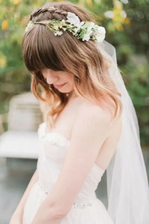 a medium length hairstyle with loose waves down, a braid on top and bangs plus a long veil