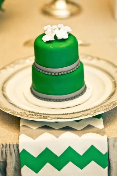 an emerald mini cake decorated with grey beads and ribbons and sugar blooms on top