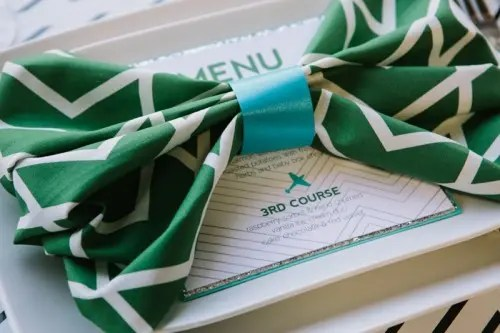 an emerald and white napkin with a geometric print and a blue bow