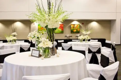 white tablecloths, white chair covers and blakc bows for a formal wedding hall