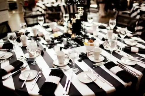 a stylish black and white wedding tablescape with a striped tablecloth, black and white napkins and a centerpiece