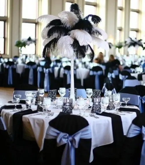 a chic black and white table setting with a tablecloth, runners, napkins and a feather centerpiece