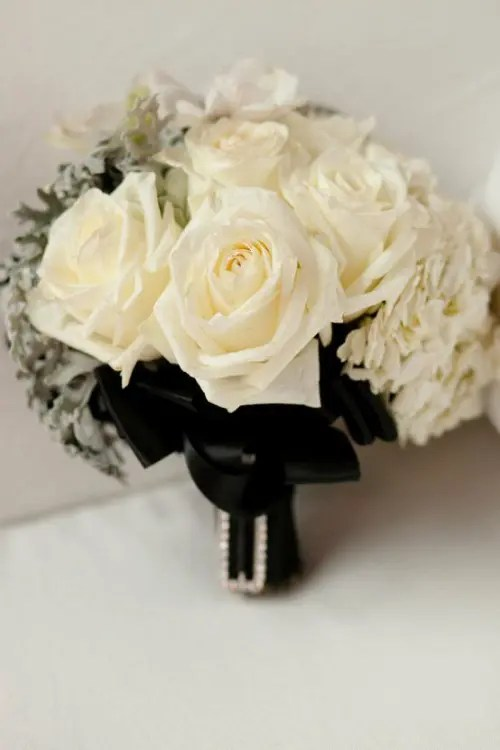 a white rose wedding bouquet with pale millet and black bows