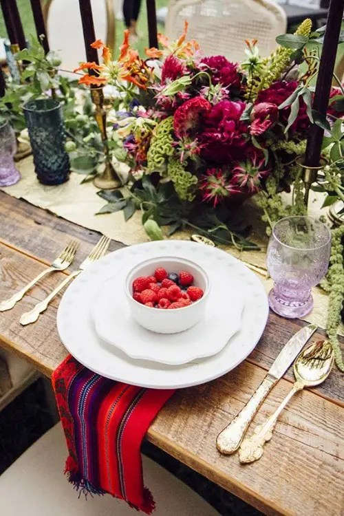 a boho tablescape with a gold table runner, black candles, colored glasses, bright florals and a colorful napkin
