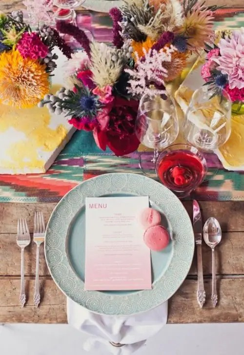 a colorful tablescape with bright textiles, colored plates and glasses and colorful florals