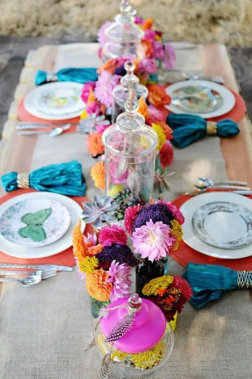 a colorful tablescape with a burlap tablecloth, colorful plates and napkins plus colorful florals