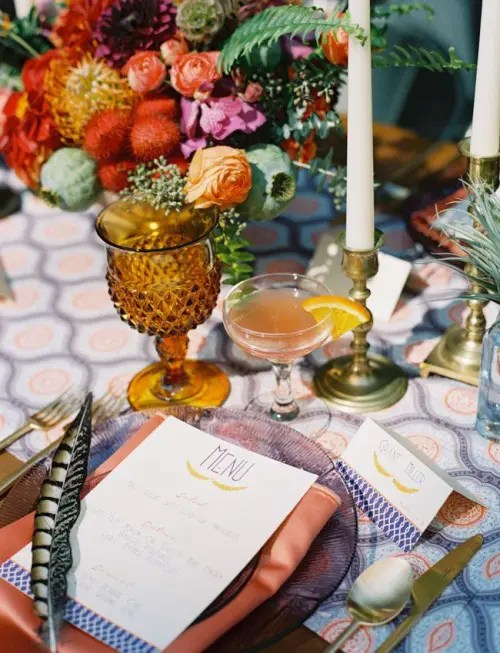 a colorful tablecloch, colorful glasses and plates, candles and super bright floral centerpieces