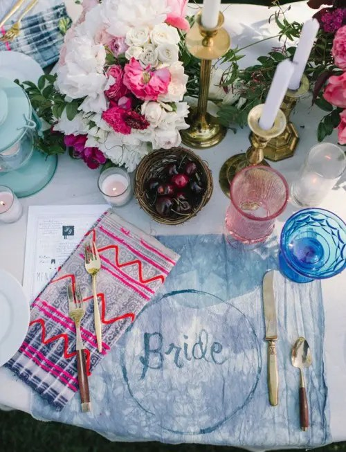 a bright table setting with colorful tie dye textiles, colored glasses and bright florals