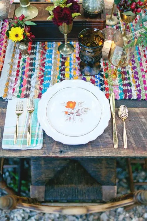 a colorful yarn table runner, bright napkins, colored glasses and bright blooms plus gold cutlery