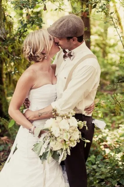 a stylish retro groom's look with chocolate brown pants, a white button down, neutral suspenders, a printed bow tie and a cap