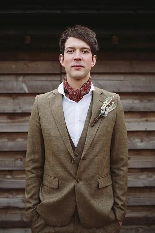 a brown three-piece wedding suit, a white button down, a red neck tie and a boutonniere