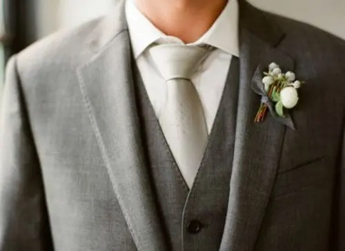 a grey three-piece suit, a white button down, a shiny silver tie and a white floral boutonniere