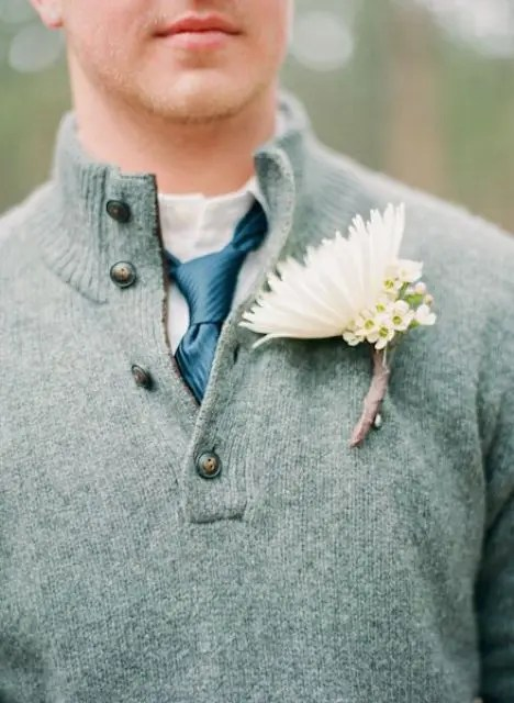 a white button down, a blue tie, a grey sweater over the shirt and a white floral boutonniere for a more casual look
