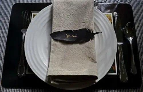 a black and white place setting with a whiet plate and neutral napkin plus a black feather place card