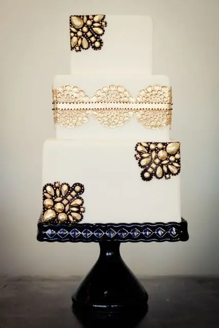 a white wedding cake decorated with gold edible lace and gold rhinestones and black lace