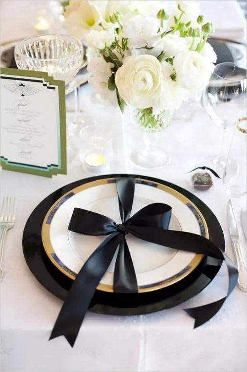 a black and gold place setting and a white tablescape with blooms