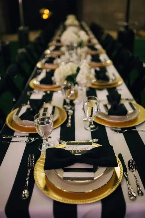 a chic tablescape with a striped tablecloth, black chargers and cutlery, striped menus and black bows