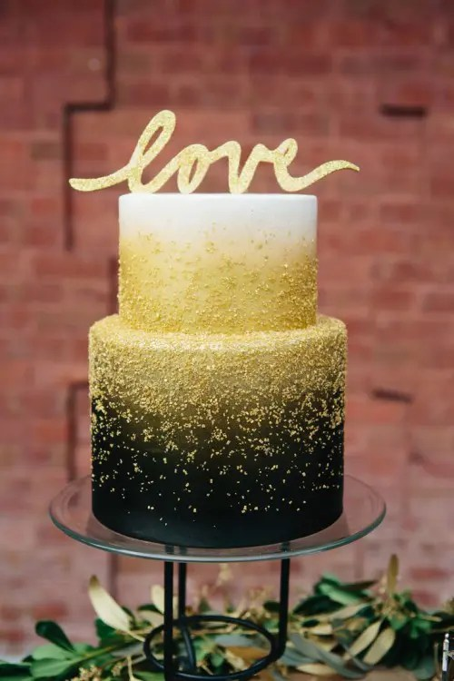 a black and white wedding cake decorated with gold glitter and with a gold glitter topper