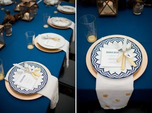 3b0aa6c6 a navy, gold and white wedding tablescape with candle lanterns and pinecones