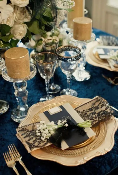 2f692567 a navy, gold and white tablescape, candles, gold rim glasses and a setting