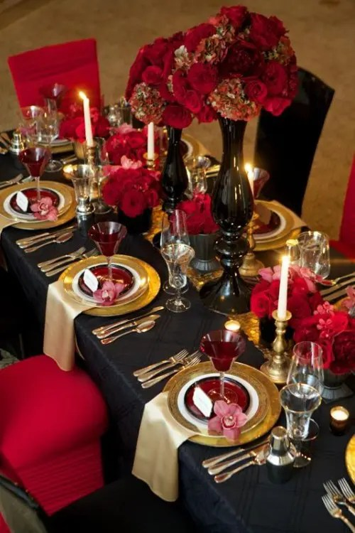 a Gothic wedding tablescape done in black, red and gold, with candles, red glasses and lush florals