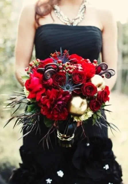 a black strapless wedding dress with a lush wedding bouquet of red blooms and dark and green foliage