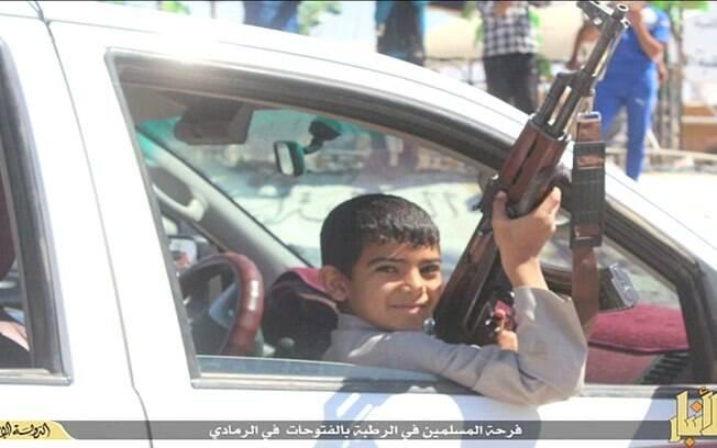 Criança com arma de fogo em mãos participa de parada comemorativa do EI em cidade do Iraque  (maio/2015). Foto: Reprodução/Youtube