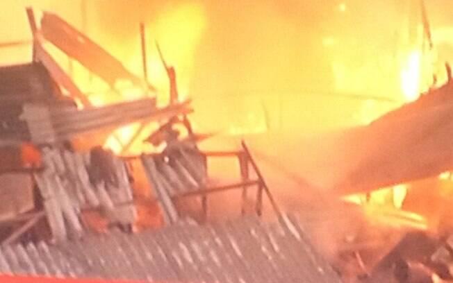 Morador (no canto direito da foto) tenta salvar pertences durante incêndio, neste sábado (7)