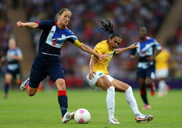 Casey Stoney battles for the ball with Marta during the Women's Football first round Group E Match between Great Britain and Brazil