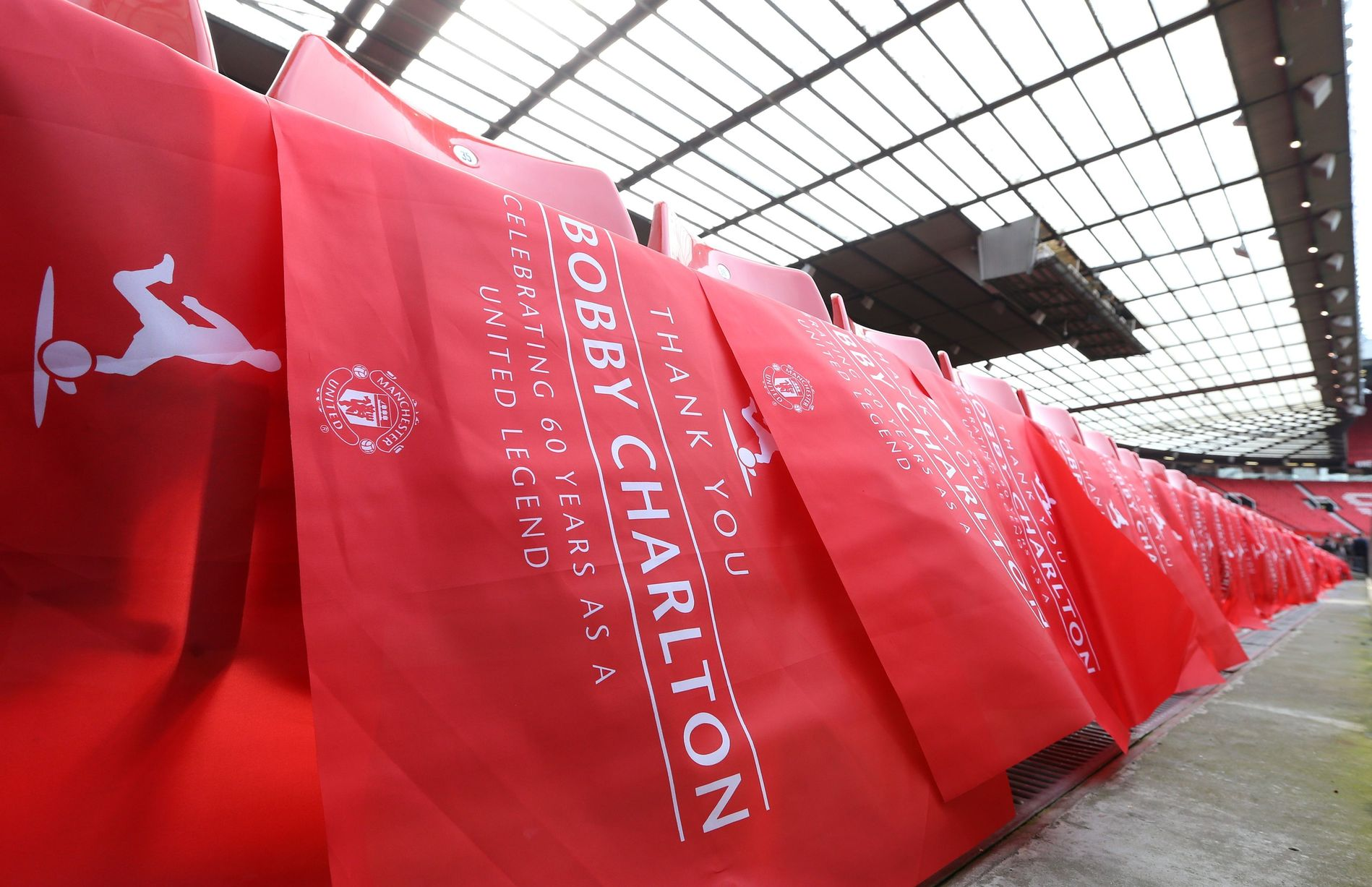 Flags are placed on seats in the Old Trafford South Stand, to be renamed The Bobby Charlton Stand. Martin Rickett/PA Wire.