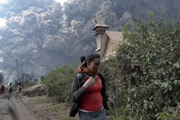 A woman flees as Mount Sinabung erupts