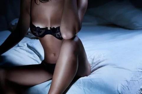 Alluring Korean woman in lingerie sitting in bed
