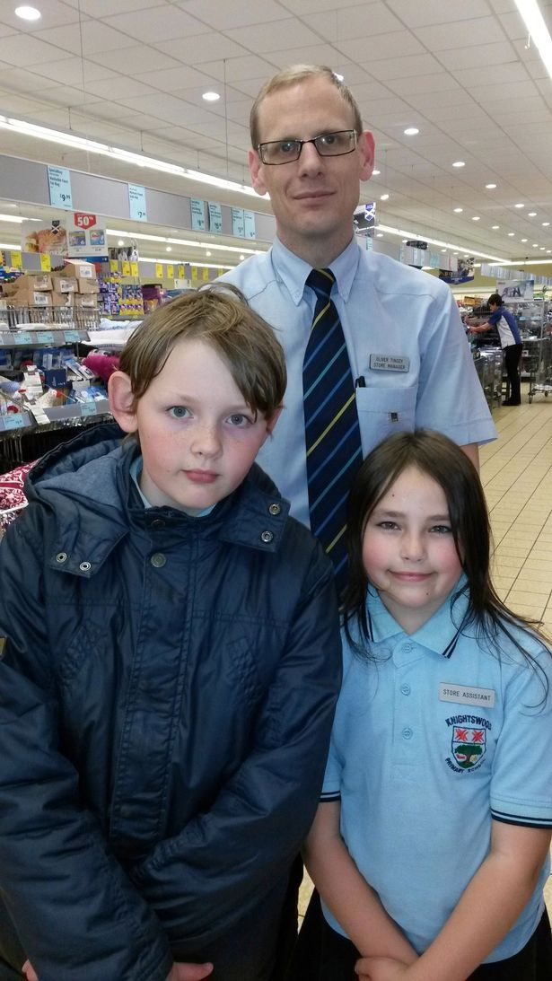 8-year-old Carina Brooks has landed a 'job' at Aldi and is being paid in fizzy sweets. She is pictured with her brother Carrick and store manager Oliver Tingey