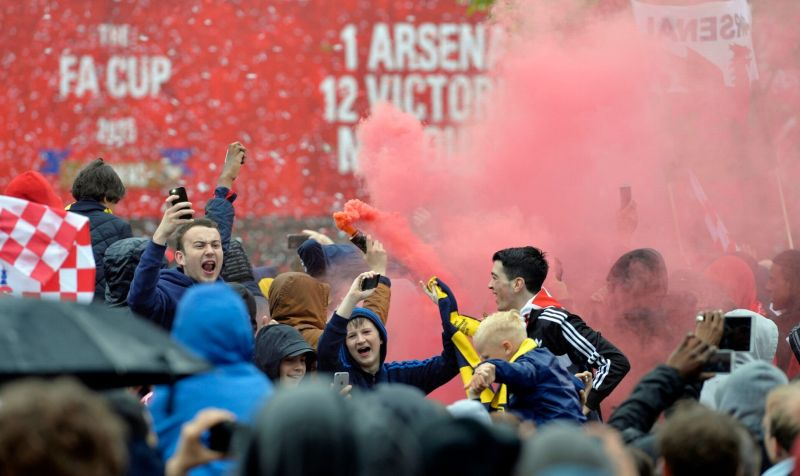 Arsenal fans celebrate during the parade