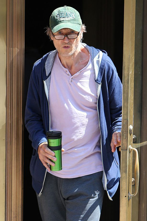 Liam Neeson steps out wearing a hooding and fleece on a hot summer day in New York City