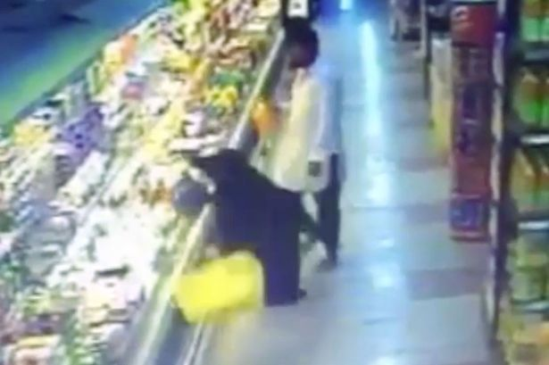 A woman is shoved out of the way by a man in Saudi Arabia