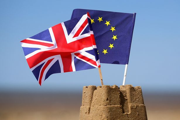 European Union and the Union flag sit on top of a sand castle