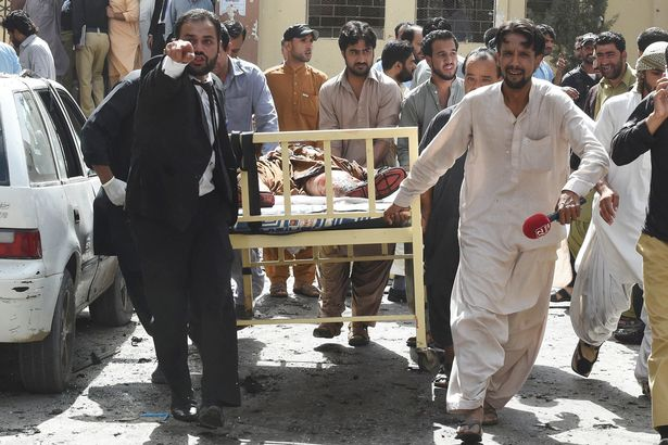 Pakistani lawyers and local media personnel carry a bed to move the body of a news cameraman after a bomb explosion at a government hospital premises in Quetta