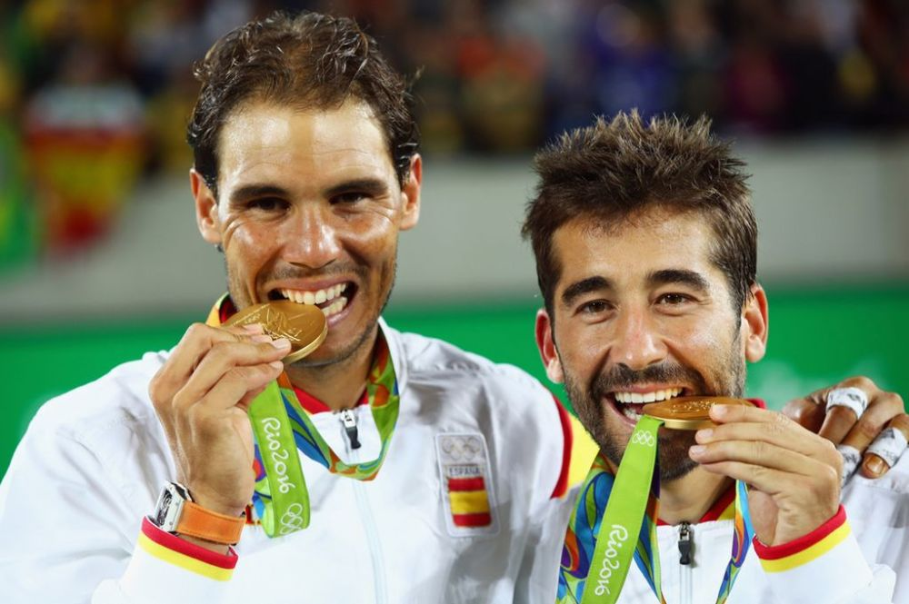 Gold medalists Rafael Nadal and Marc Lopez celebrate with their medals