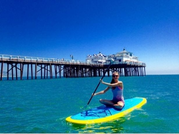 Alyssa Ramos paddle boarding in California on one of her travel dates