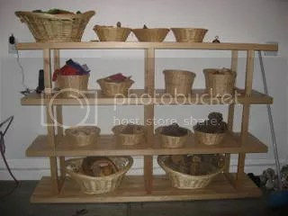 Each toy has its own space, and many are ojects like seashells and pine cones collected from nature. The bottom two baskets are filled with blocks made from sections of treetrunks and branches.
