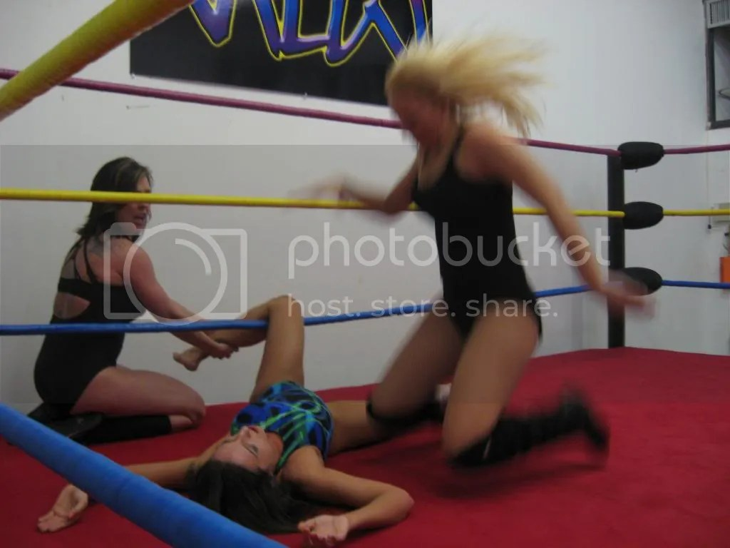 Christie Ricci holds and wrings the left leg of Nikki St. John along the bottom ring rope as Amber O' Neal sia bout to deliver a jumping right karate chop to her throat photo IMG_3162.jpg