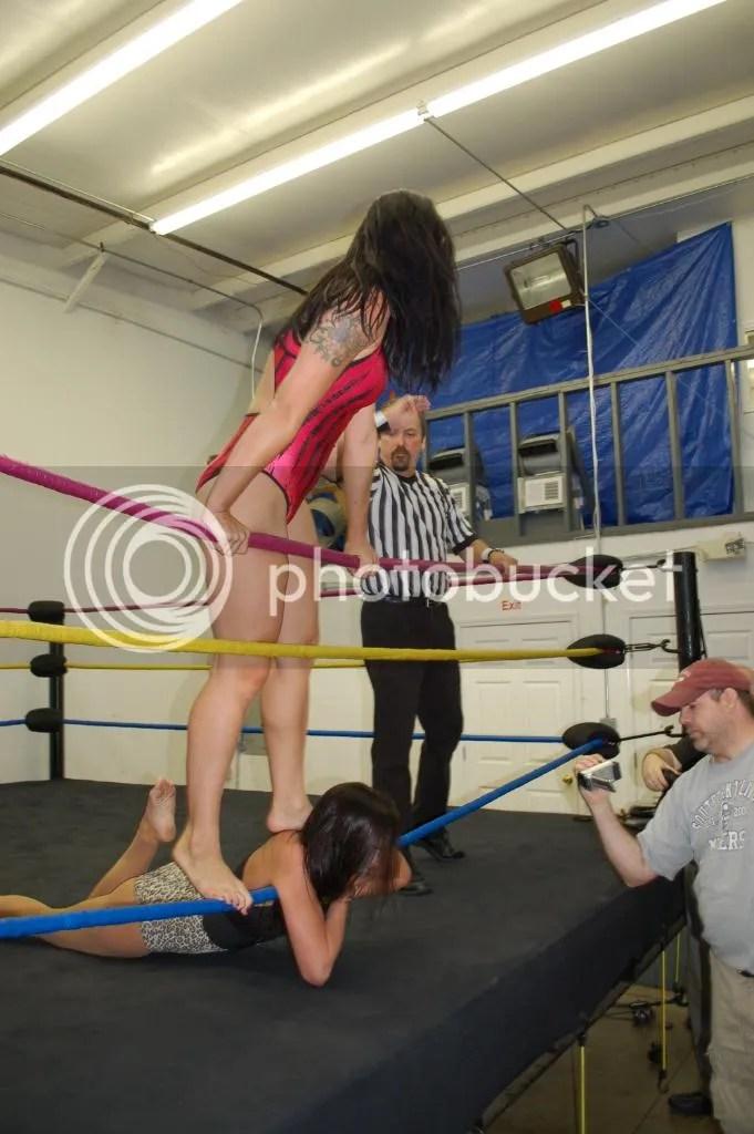 """Smokin' HOTT"" Nikki Lane relentlessly continues standing on the back of Santana Garrett while illegally choking her throat along the bottom ring rope photo DSC_0437.jpg"