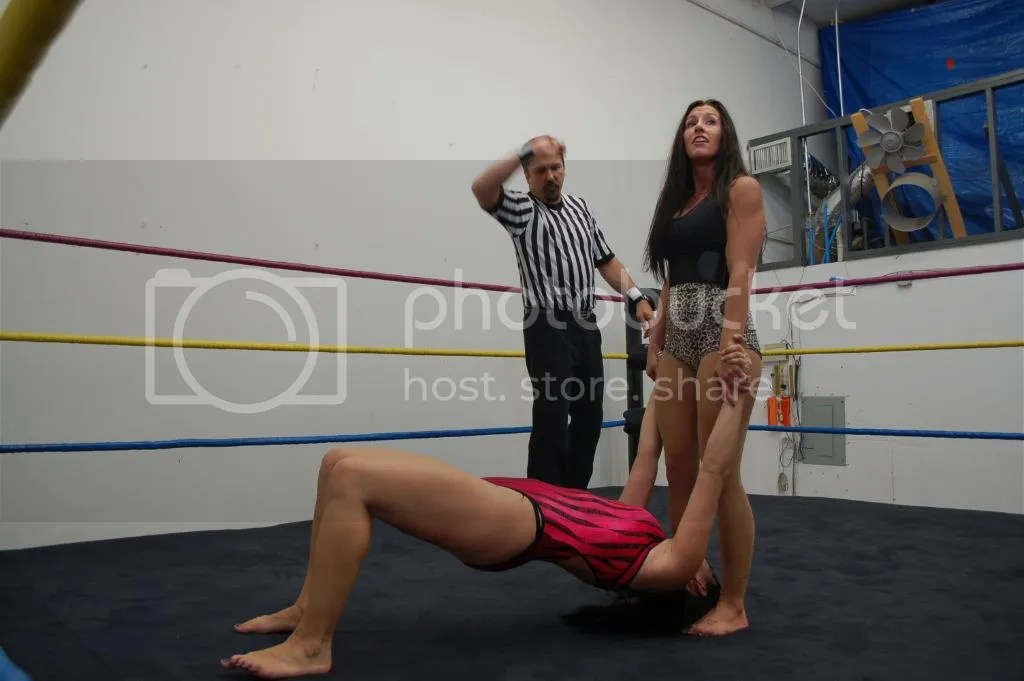 "Santana Garrett is milking the count of Magnificent Ladies Wrestling Scott Stevens to her advantage with her pulling of the arms and her standing on the hair of ""Smokin' HOTT"" Nikki Lane photo DSC_0494.jpg"