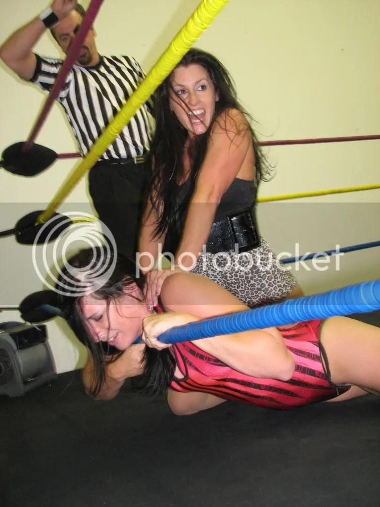 """Santana Garrett is illegally choking the throat of """"Smokin' HOTT"""" Nikki Lane along the bottom ring rope photo IMG_1852.jpg"""