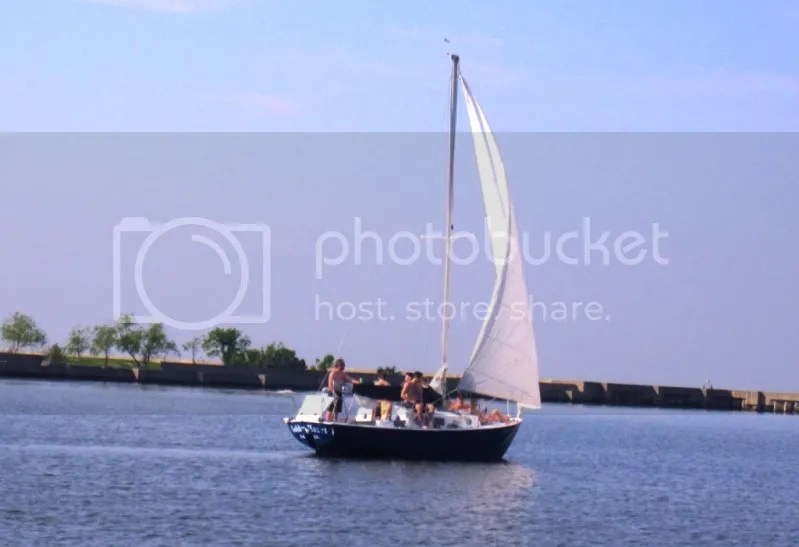 Sailboat full of people headed out on the lake